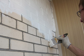 нанесение водоэмульсионной краски на кирпичную стену